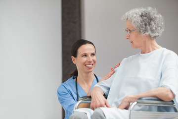 Smiling nurse looking at a senior patient in a wheelchair