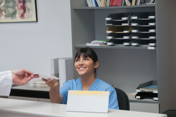 Nurse behind a desk giving a paper to a doctor