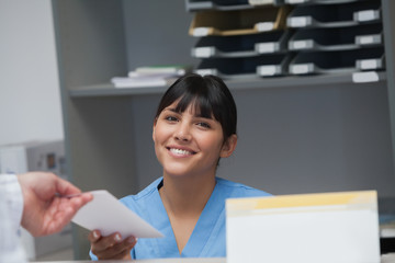 Nurse smiling while holding a paper