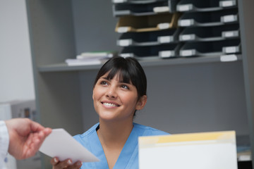 Smiling nurse behind a desk giving a file to a doctor