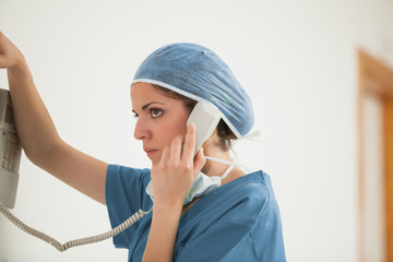 Surgeon using a phone in a hallway