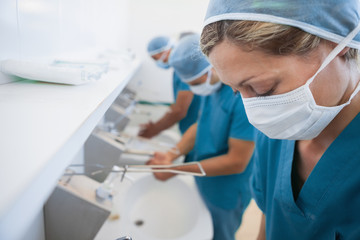 Female surgeon in a hospital washoom washing her hands