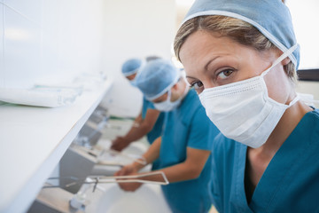 Female surgeon in a hospital washroom washing her hands with a mask