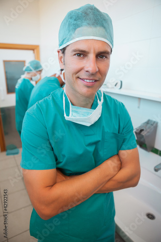 Smiling surgeon with his arms folded