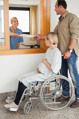 Nurse giving a paper to a man and a pregnant woman in a wheelchair