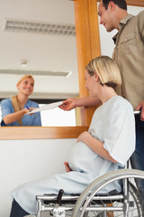 Smiling nurse giving a paper to a man and a woman in a wheelchair