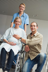 Pregnant woman in a wheelchair with a nurse and a man