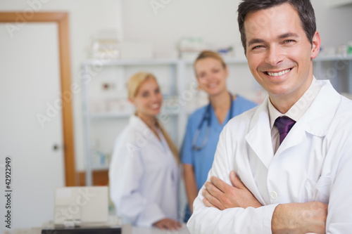 Pharmacist standing in a pharmacy with co-workers