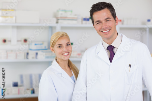 Two pharmacists standing behind a counter