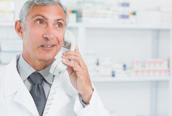 Pharmacist talking on the phone in a pharmacy