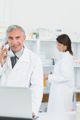 Smiling pharmacist talking on the phone standing in a pharmacy