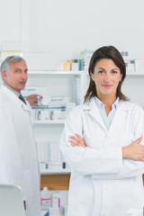 Woman pharmacists with her arms crossed and a colleague