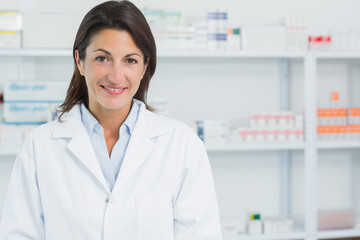 Smiling female pharmacist standing in a pharmacy