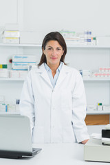 Female pharmacist standing in a pharmacy with a laptop