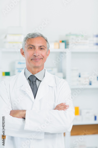 Pharmacist with his arms crossed standing in a pharmacy