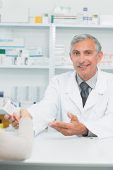 Happy pharmacist giving pills to a customer