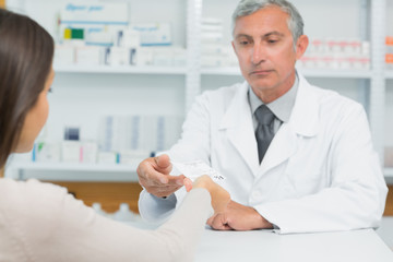 Male pharmacist receiving a prescription from a customer