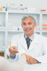 Smiling pharmacist taking a prescription from the hand of a customer