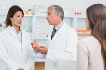 Pharmacist talking to a colleague in front of a patient