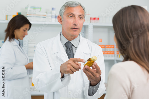 Pharmacist talking to a customer while holding a flask of pills