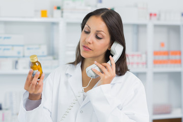 Female pharmacist holding a bottle of pills while on the phone