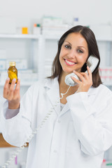 Smiling female pharmacist holding a bottle of pills while phoning
