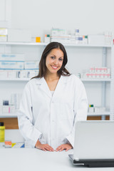 Smiling pharmacist standing behind the counter of a pharmacy