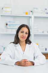 Smiling female pharmacist joining her hands on the counter of a pharmacy