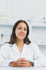 Female pharmacist joining her hands on the counter of a pharmacy