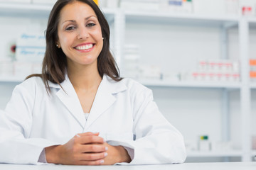 Female pharmacist joining her hands behind the counter of a pharmacy