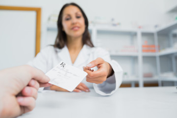 Female pharmacist receiving a paper from a customer