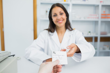 Happy pharmacist receiving a prescription from a customer