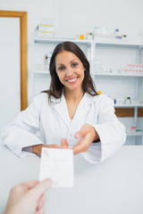 Happy female pharmacist receiving a prescription from a customer