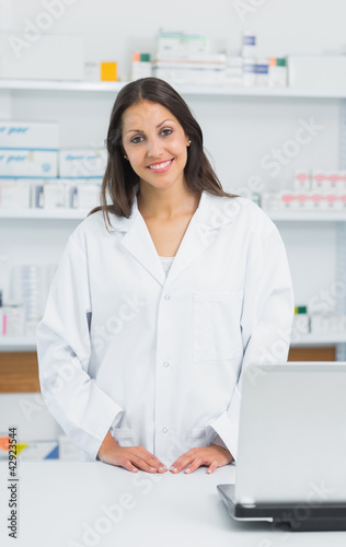 Smiling female pharmacist standing behind the counter of a pharmacy
