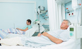 Two male patients lying on hospital beds