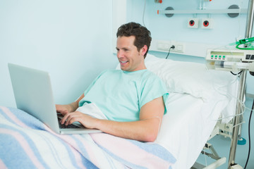 Joyful patient typing on a laptop while lying on a bed
