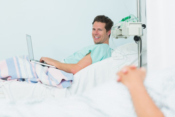 Focus shot of a smiling male patient typing on a laptop while lying on a bed