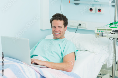 Joyful patient with a laptop lying on a bed