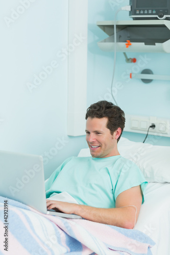 Joyful patient using a laptop while lying on a bed