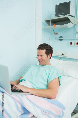 Joyful male patient using a laptop while lying on a bed