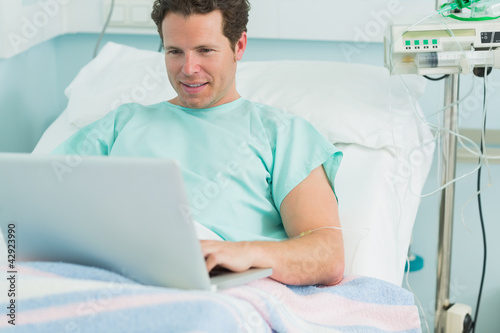 Happy male patient typing on a laptop while lying on a bed