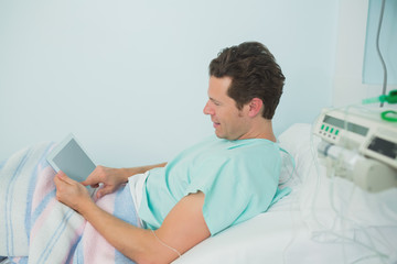 Male patient touching a tactile tablet while lying on a bed