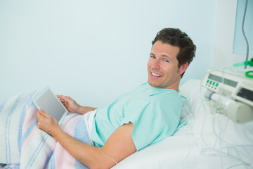 Smiling male patient touching a tactile tablet while lying on a bed