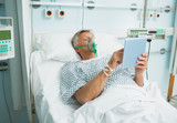 Patient lying on a bed with a mask while holding a tactile tablet