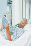 Senior male patient wearing an oxygen mask while holding a tactile tablet in his hands