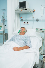 Patient lying on a bed with an oxygen mask