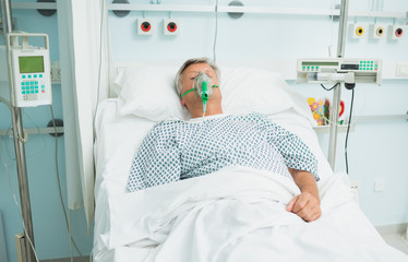 Unconscious male patient lying on a bed with an oxygen mask