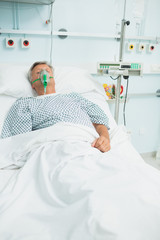 Conscious senior male patient lying on a bed with an oxygen mask