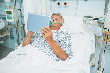 Male patient lying on a bed with a mask while holding a tactile tablet