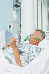 Senior male patient wearing an oxygen mask while using a tactile tablet